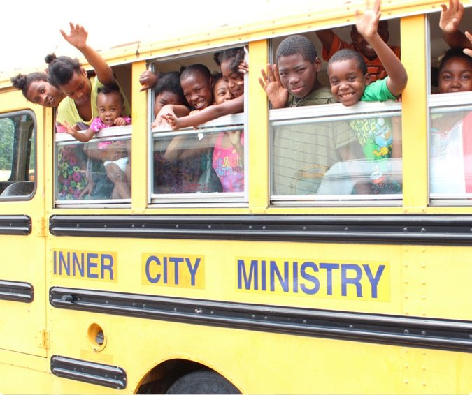 Children Waving on a Bus