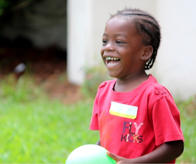 Closeup of Child Holding a Ball and Smiling